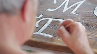 Painting letters on wooden plank. Close up old hand drawing with white color brush on wooden plank.