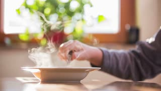 Person cooling hot dinner.Beautiful kitchen scene with person holding spoon and mixing hot soup with steam ascending. Bright window in background with green flower.