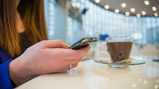 Person eating hot chocolate with spoon. Low angle close up of female person on smartphone in cafe eating hot chocolate from glass.