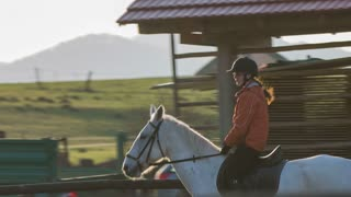 Person enjoying riding horse at sunset. Woman training horse ride outdoors with trainer in the middle.
