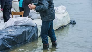 Person in rubber boots standing in flooded water. Man with photo camera in hands walking deeper in to flooded water with sandbags in background.