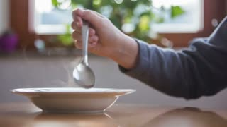 Person mixing hot soup.Close up of person in kitchen mixing hot soup with spoon to cool it down.