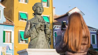 Person photographing famous statue. Brown long haired woman with smartphone taking picture of Baldassare Galuppi statue  on Burano square on a sunny day. Shot from the back.