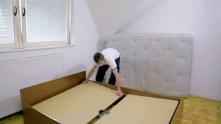 Person removing big wooden desks from old sleeping bed. Wide angle of empty room only with old sleeping bed and male putting it apart.