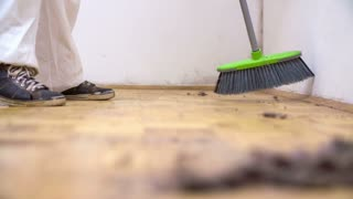 Person sweep room with dust. Household cleaning with sweeper, a lot of dust with mites and hair on floor.