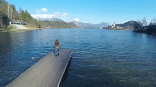 Person walk on lake pier aerial fly around 4K. Beautiful landscape view from wooden pier, female woman walking to the edge looking around and turning back. Flying around with quadcopter.