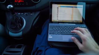 Person working on computer while driving in car. Passenger first person view while typing on small laptop in car.