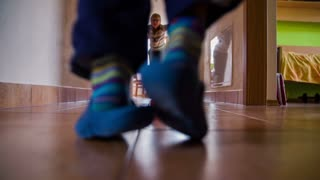 Playing in the hallway of home in slow motion. Two boys playing soccer in house hallway between rooms, with kitchen in the background.