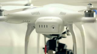 Powering small white flying drone quadcopter. Turning on aerial device making starting sounds and adjusting camera head.
