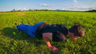 Push-ups on grass field. Teenager doing exercise in nature, slow motion crane shot.