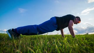 Push-ups Wide Shot in Slow Motion. Teenager doing exercise in nature, slow motion crane shot.