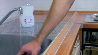 Putting detergent for washing dishes on sponge. Young attractive man in new home, checking and cleaning kitchen before using with own dishes.