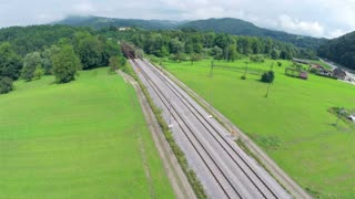 Railway tracks aerial footage. Aerial flight over railway tracks with bridge over river.