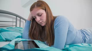 Reading content on tablet PC while lying on bed. Attractive young woman with red hair and long nails lying on bedroom bad and playing/typing on tablet computer. Slow motion jib shots.