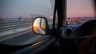 Reflecting sunset in car mirror. Driving on road with view on drivers side mirror with sunset shining.