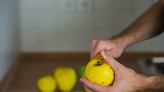 Removing peel from yellow apple. Person peeling sweet yellow apple with ceramic sharp knife from top to bottom.