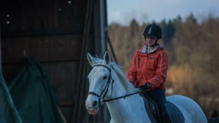 Riding horse in to camera. Attractive woman in orange jacket riding on white horse towards the camera.