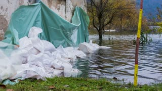 Sand bags around the house walls saving from flood. Flooding disaster after massive rainfall, houses in danger of being flooded.