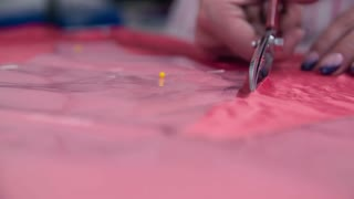 Scissors cutting textile front shot slow motion close up. Tailor cutting pieces from blank textile for new elegant dress with measured plastic foils.