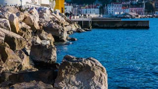 Sea coast with big rocks and pier. Side shot of blue sea surface with big rocks and pier.