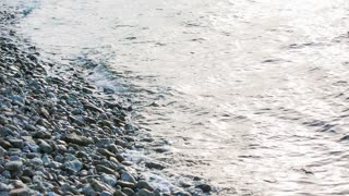 Sea hit pebble beach. Close up view of rocky beach and sea waves watering them over.