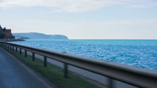 Sea landscape from car vehicle. Shot from inside vehicle while driving beside the sea on a sunny day.