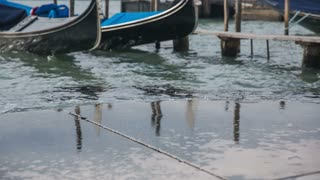 Sea splashing in to harbor. Wavy sea in Venice with gondolas throwing all around in background.
