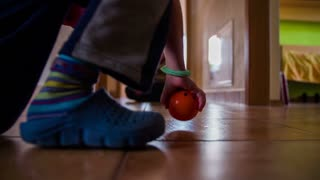 Setting and kicking ball in door goal at home. Kids playing soccer at home with doors being as goal and small soft ball with smile. Shot at low angle slow motion.