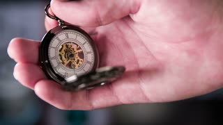 Setting Pocket Watch Ticking in Slow Motion. Small pocket clock in man hands close up.