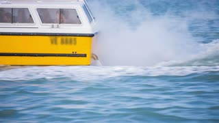 Ship back while speeding on sea. Riding alongside with fast boat speeding through sea water with motors in the back spitting water.