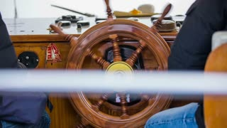 Ship retro steering wheel. Medium shot of person steering old fashioned rudder on a ship.