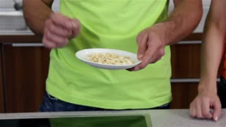 Showing Seeds Dish For Healthy Life. Plate with special seeds in man hands explaining and putting it back to other seeds in small bowls. Kitchen cooking healthy food.