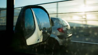 Side car mirror while passing on highway. Close up shot of car side mirror while driving on highway and passing a slower car.