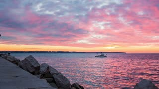 Small boat sail on sea after sunset.Wide shot of colorful sea and clouds after sunset while a small fishing boat sail across.
