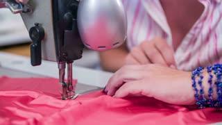 Small business sewing studio making dress on machine close up. Woman with beautiful nails working on a dress with sewing machine in slow motion.