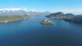 Small island in the middle of the lake 4K. Aerial shot of famous church on island in the middle of blue Bled lake. Beautiful sunny day with reflection of blue sky, alps in background.