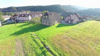 Small village at sunset with two boys walking dog aerial footage. Flying above countryside fields with houses in front and two people walk dog between in slow motion.