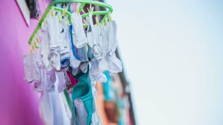 Socks and underwear drying outside. Drying clothes on a sunny day, handing from colorful building in Burano, Venetian Lagoon town on sea.
