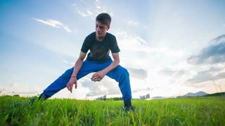 Stretching At Sunset. Wide landscape shot of young man in blue tracksuit and music in ears doing stretching exercise.