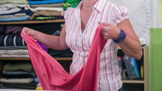 Stretching pink textile over whole table slow motion. Tailor throwing big textile piece over the table before cutting to parts for dress.
