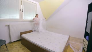 Stretching plastic foil to cover sleeping bed. Wide shot of room before paint job, woman protecting furniture against drops of color.