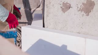 Styrofoam around walls close up. Person putting Styrofoam around house walls close up on hands trying measures of big block against wall.