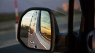 Sunset in car side mirror. Close up of car mirror while driving and sunset view behind the vehicle.