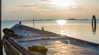 Sunset with seascape from boat deck. Static shot of sun going down, shining on boat and sea, beautiful scenery.