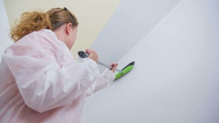 Sweeping walls with broom in slow motion. Woman cleaning away dust and spider webs from room walls before starting painting with fresh white color.