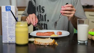 Table with hot-dogs, mustard and milk close up. Person cutting hot-dogs on plate with knife and fork, with prepared mustard and milk and bread.