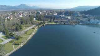 Tourism spot around lake Bled on a sunny day aerial 4K. Flying over lake Bled with panorama view on village, forest and mountains far away.