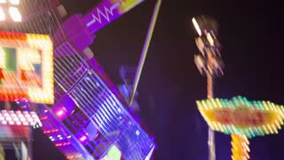 Tracking rotating ride in amusement park. Night shot of fun and entertaining ride rotating around axis in air with people riding close up.