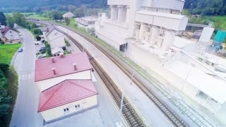 Train far away arriving at station aerial footage. Train traveling on railroad arriving at station with factory next to it.