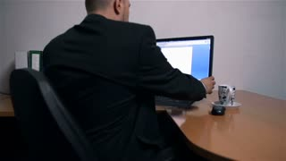 Turning Off Computer And Businessman Getting Ready to Go Home
